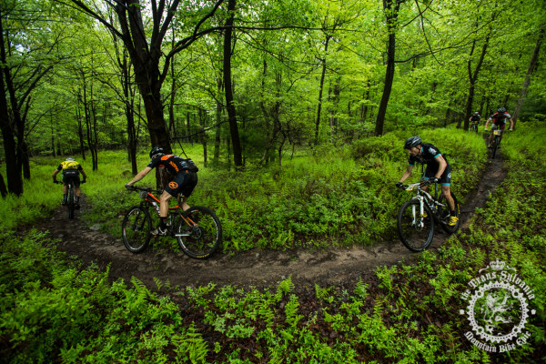 Riders make their way through flowy singletrack between road sections on stage 4.