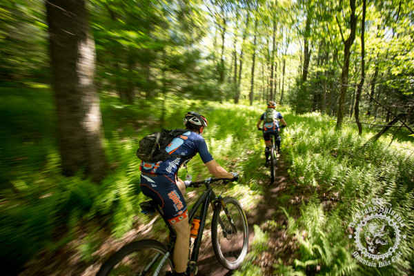 Two riders on the fern lined trails near the campground section of Stage 7