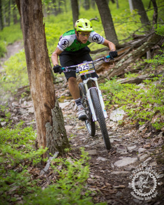 Cody Philips dodges a trailside tree during a downhill enduro section