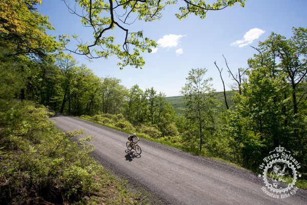 Barry Croker descends a gravel road in sight of a valley backdrop