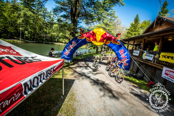 A string of racers pull through the finishing arch of the final stage of the Trans-Sylvania Epic