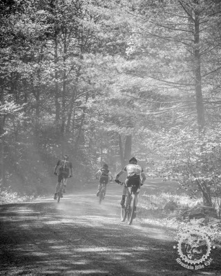 Riders race through dusty gravel roads.