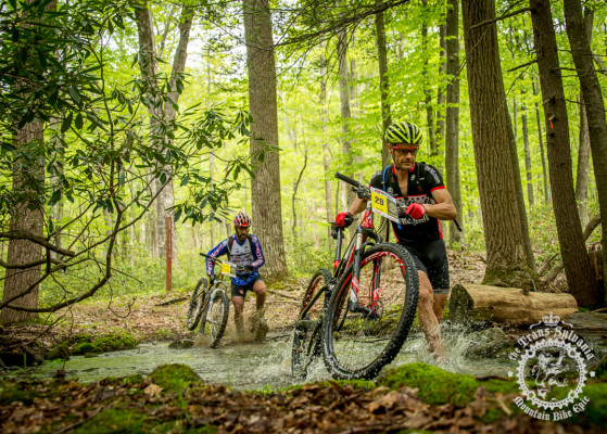 Two riders cross a stream during the 2014 NoTubes Trans-Sylvania Epic mountain bike stage race.