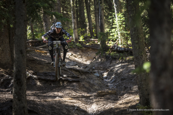 Fully pinned through the slippery, muddy roots. Loose is fast in these conditions. Photo credit: Devon Balet