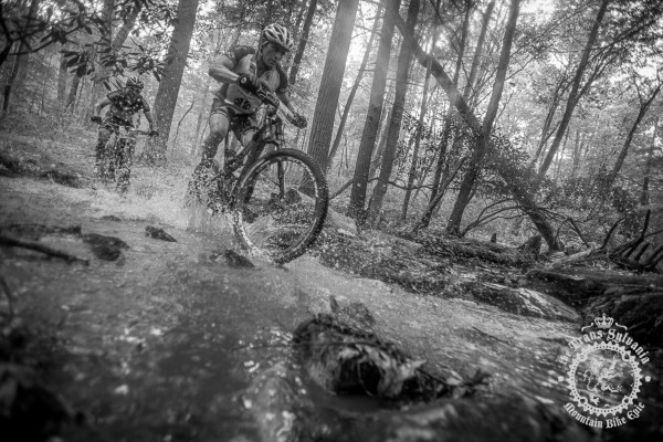 Two men ride through a stream crossing at the end of the second timed segment in the enduro stage at the No