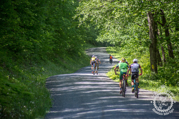 Riders pass by some abandoned buildings along the race course at the NoTubes Trans-Sylvania Epic.