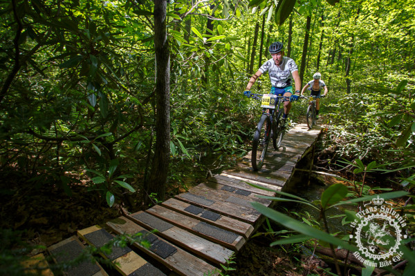 Drew Dillman and Scott Smith cross a heavily wooded stream in the NoTubes Trans-Sylvania Epic.