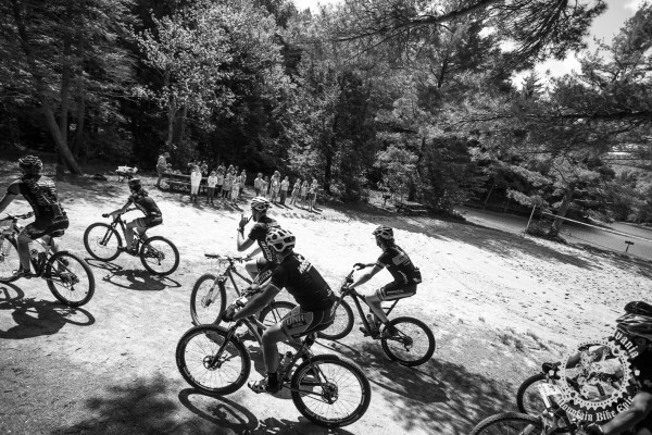 Riders roll past a group of elementary school students at the NoTubes Trans-Sylvania Epic.